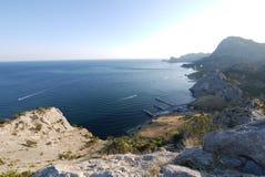 Un pilastro al piede di alta montagna rocciosa vicino che le barche fanno galleggiare Immagini Stock Libere da Diritti