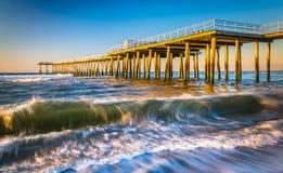 Un pilastro ed onde di pesca nell'Oceano Atlantico ad alba, in VE Fotografie Stock