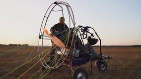 Un pilota dell'uomo di un aliante del motore attacca il paracadute al corpo dell'aliante che prepara per il volo e controllare video d archivio