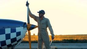Un pilota pulisce un'elica di piccolo aeroplano archivi video