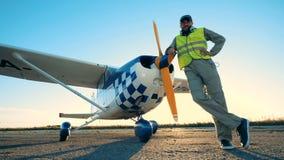 Un pilota sorride ad una macchina fotografica, stante vicino ad un aereo, fine su video d archivio