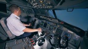 Un piloto da vuelta a un avión al izquierdo, sentándose en un simulador de vuelo 4K almacen de video