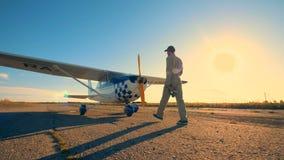 Un piloto que camina en un campo de aviación para controlar un aeroplano, cierre metrajes