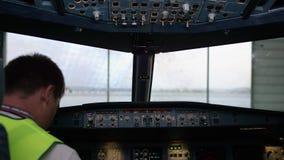 Un piloto que comprueba los instrumentos en una carlinga plana Vista posterior de los controles de funcionamiento del piloto del  almacen de metraje de vídeo