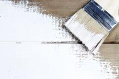 Un pinceau avec la peinture blanche sur un fond peint en bois, l'espace de copie, vue supérieure photographie stock libre de droits