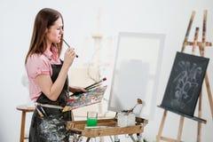Un pintor de la mujer joven en un estudio blanco brillante dibuja una imagen en lona en un caballete fotos de archivo libres de regalías