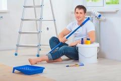 Un pintor de los hombres jovenes que se sienta en el piso que sostiene el paintroller y el retrete Fotos de archivo