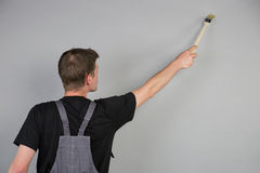 Un pintor está utilizando un cepillo sobre su cabeza para pintar la pared Fotos de archivo libres de regalías
