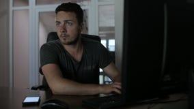 Un pirata informático corta un ordenador y mira alrededor metrajes