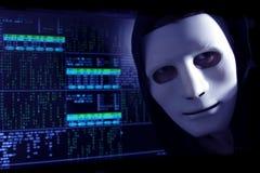 Un pirate informatique dans un masque sur un fond de code binaire examine le cadre Photos libres de droits