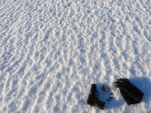Un pistolet et balles de 9mm avec les gants noirs dispersés dans la neige images libres de droits