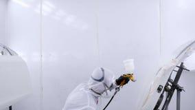 Un pittore professionista dell'automobile sta dipingendo un lavoro di corpo stock footage