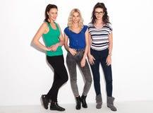 Un pixture pieno del corpo di tre giovani donne felici Immagini Stock