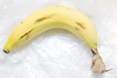 Un plátano en una bolsa de plástico Foto de archivo