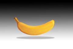 Un plátano que flota en el aire con una sombra abajo Imágenes de archivo libres de regalías