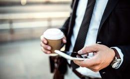 Un plan rapproché d'un homme d'affaires avec le smartphone et le café dans la ville, textotant photo stock