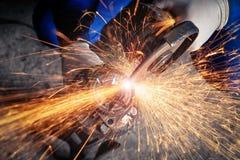 Un plan rapproché d'un mécanicien de voiture utilisant une broyeur en métal photo stock