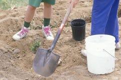 Un plan rapproché d'une femme et d'une petite fille plantant un arbre Images stock