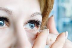 Un plan rapproché d'une femme insérant un verre de contact dans son oeil images libres de droits