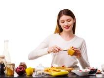 Un plan rapproché d'une fille avec un couteau sort un lait condensé pour les gaufres belges avec un remplissage de banane Photos stock