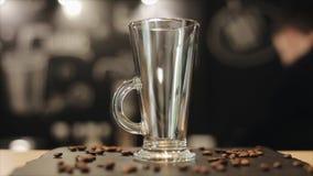 Un plan rapproché d'une tasse en verre vide pour le latte se tenant sur un compteur de barre avec quelques grains de café là-dess banque de vidéos