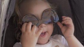Un plan rapproché d'un visage de bébés qui utilise les lunettes de soleil femelles à l'envers banque de vidéos