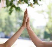 Un plan rapproché de deux mains sur un fond brouillé de parc Une main femelle donnant à cinq une main masculine Relations et amit Photo libre de droits