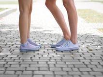 Un plan rapproché des jambes de ` de teenages dans des espadrilles blanches parlant entre eux sur un fond pavé en cailloutis brou Photographie stock libre de droits