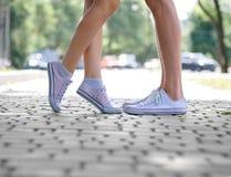 Un plan rapproché des jambes de ` de teenages dans des espadrilles blanches se tenant sur un fond naturel brouillé Copiez l'espac Image stock