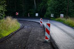 Un plan rapproché du processus de réparer la couche de surface avec l'asphalte, pare-chocs de bord de la route photographie stock libre de droits