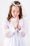 Jeune fille priant dans le premier vêtement de communion Images stock