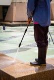 Un plancher de nettoyage d'homme avec le jet d'eau à haute pression Photo stock