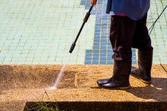 Un plancher de nettoyage d'homme avec le jet d'eau à haute pression Images stock