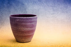 Un planta-pote púrpura de la arcilla contra un fondo azul y amarillo Imágenes de archivo libres de regalías