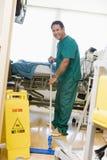 Un planton essuyant l'étage dans un hôpital Images libres de droits