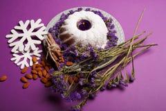Un plat avec un gâteau d'anneau, allumé bougie, cannelle, amande et flocons de neige sur un fond violet lumineux, vue supérieure Photo libre de droits