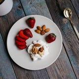 Un plat avec le fromage blanc, les fraises et les écrous, une tasse de café et serviettes sur une table en bois photos libres de droits
