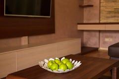 Un plat avec les pommes vertes sur la table en appartement Images stock