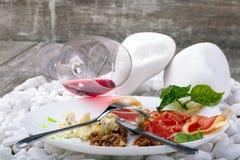 Un plat blanc avec le hamon salé, fromage bleu, noix et bazil, un verre de vin rouge sur un fond en bois en pierre blanc Images stock