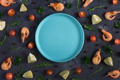 Un plat bleu vide se situe au centre d'un fond texturisé foncé Autour de sont le citron dispersé, rucola, poivre et Photos stock
