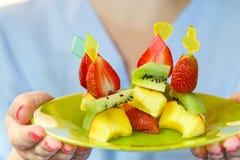 Un plat de canapé de kiwi, de fraises et de pêches dans les mains d'une femme Photo libre de droits