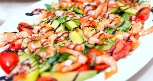 Un plat de salade avec des crevettes roses, avocat, fruits de mer, tomates dans un plat blanc Photos libres de droits
