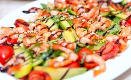 Un plat de salade avec des crevettes roses, avocat, fruits de mer, tomates dans un plat blanc Image libre de droits