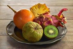 Un plat des fruits exotiques - chérimolier, kiwi, pitahaya, passiflore, ananas photographie stock