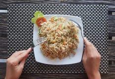Un plat des nouilles mojito en verre Cuillère et fourchette dans les mains d'une fille Vue de ci-avant photos stock