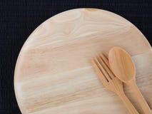 Un plat en bois vide avec les cuillères et les fourchettes en bois Image stock