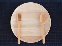 Un plat en bois vide avec les cuillères et les fourchettes en bois Photos stock