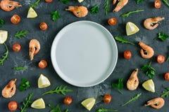 Un plat gris vide se situe au centre d'un fond texturisé foncé Autour de sont le citron dispersé, persil, rucola Image stock