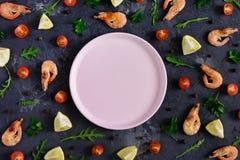 Un plat rose vide se situe au centre d'un fond texturisé foncé Autour de sont le citron dispersé, persil, poivre Photo libre de droits