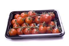 Un plateau des tomates-cerises sur la vigne Photos stock